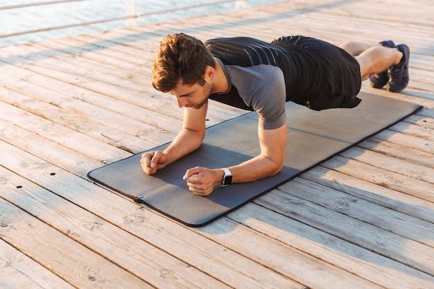 운동복에 집중된 스포츠맨은 매트에 누워 아침에 해변에서 목재 부두에서 운동하는 동안 판자를하고
