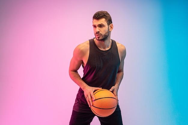 集中したスポーツマンはバスケットボールをします。若いひげを生やしたヨーロッパのバスケットボール選手がボールを保持します。青とピンクの背景に分離。スタジオ撮影。コピースペース