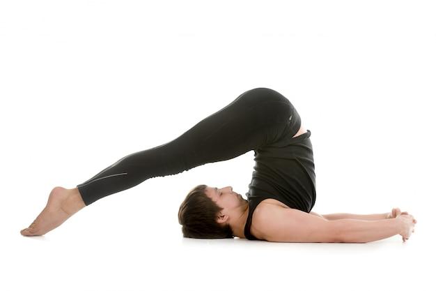 Sportivo concentrato allungando la schiena e le gambe