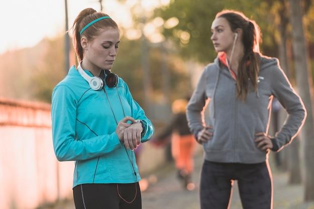 Концентрированный спортсменкой, глядя на свои часы