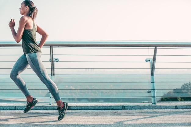 야외에서 다리를 달리면서 빠르게 움직이는 집중된 스포츠우먼. 웹사이트 배너