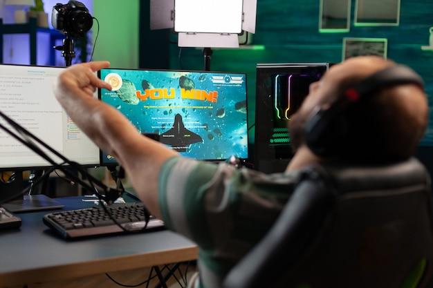 最新のヘッドセットを使用した集中ストリーマープレイスペースシューティングゲーム。ゲームトーナメント中に強力なプロのコンピューターで実行するオンラインストリーミングサイバー