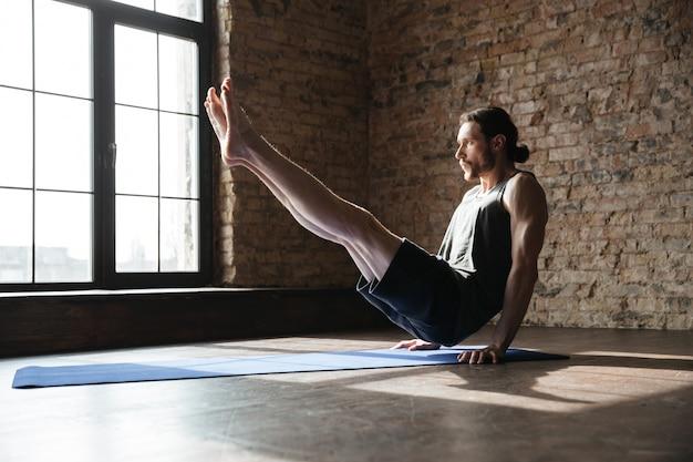Lo sportivo forte concentrato in palestra fa esercizi sportivi di yoga.