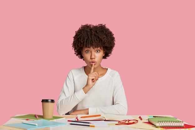 Ragazza studentessa concentrata in posa alla scrivania contro il muro rosa