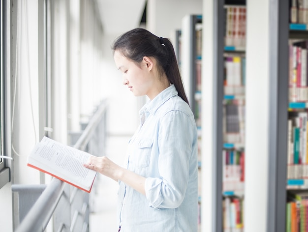 Concentrated student reading a book with bookshelves background