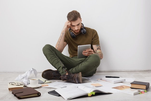 Concentrated stylish hipster guy with tattooed arms, sits crossed legs on floor, surrounded with many books and papers