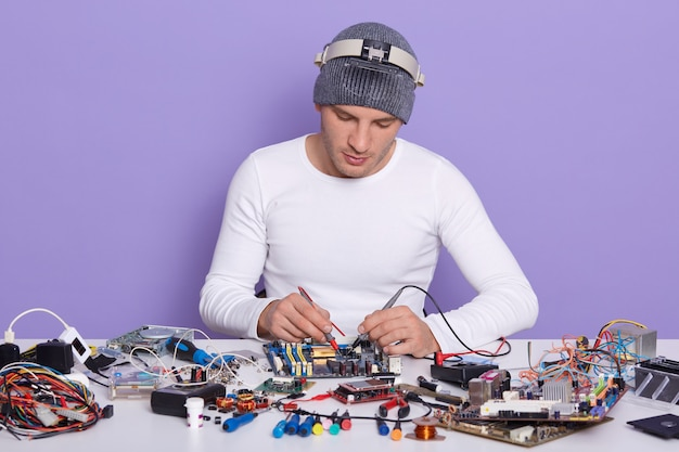 Tecnico concentrato che ripara all'interno dello smartphone o del computer portatile dal multimetro in laboratorio