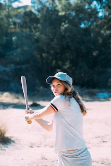 Concentrated teen student swinging baseball bat