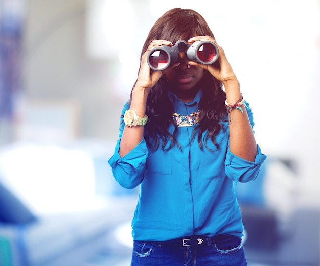 Concentrated teen using her binoculars