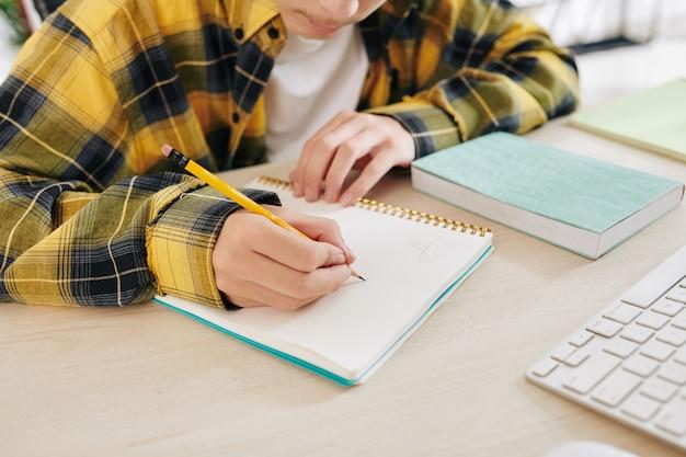 Сосредоточенный подросток делает наброски для своего школьного проекта в тетради