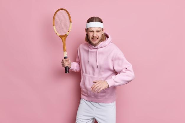 집중된 테니스 선수가 라켓을 들고 운동복을 입고 경기를 시작할 준비를하고있다.