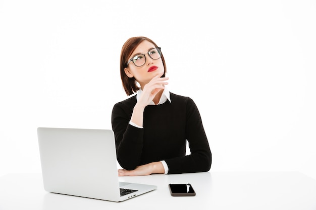 Concentrated thinking young business lady using laptop computer