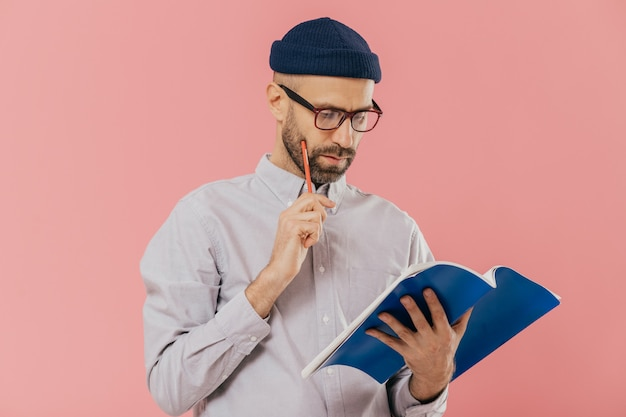Concentrated unshaven adult man holds blue textbook and pencil, reads necessary information