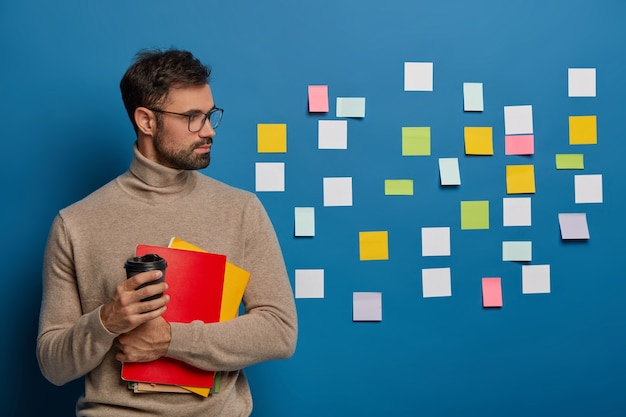 Concentrated unshaven guy has coffee, turns away on blue wall with adhesive colorful notes, has much work and tasks