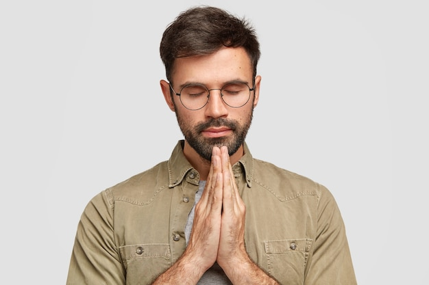 Concentrated unshaven man stands in praying gesture, keeps palms pressed together
