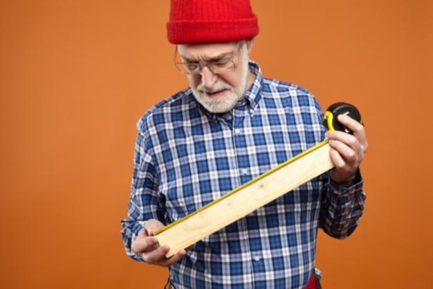 Falegname in pensione con la barba lunga concentrato che indossa cappello rosso lavorato a maglia, cintura degli attrezzi e camicia a quadri che fa mobili, che tiene la tavola di legno e il nastro di misurazione. artigianato, lavoro, occupazione, età e pensionamento
