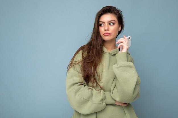 Сосредоточенная расстроенная привлекательная молодая женщина в стильной толстовке с капюшоном держит с помощью мобильного телефона, изолированного на фоне, глядя в сторону, имея идею и мечтать. копировать пространство