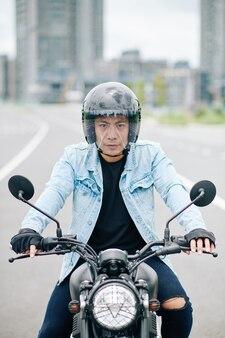 高速道路でバイクに乗ってヘルメットをかぶった集中ベトナム人男性