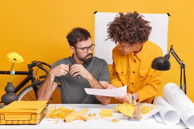 集中した女性と男性が、現代のオフィスでの勤務時間中にデスクトップでの情報ポーズで協力し、青写真に囲まれた建築プロジェクトについて話し合います