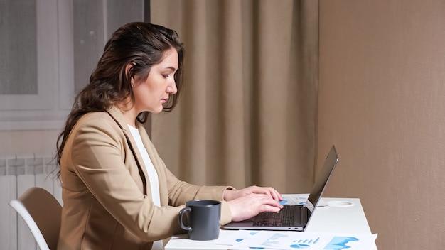 Сосредоточенная женщина-фрилансер с длинными распущенными волосами на сером ноутбуке смотрит в дисплей и сидит за столом с чашкой кофе в комнате