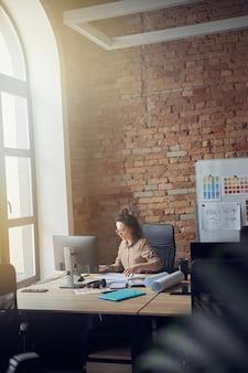 안경 전문 건축가나 디자이너가 청사진에 앉아 작업하는 집중된 여성