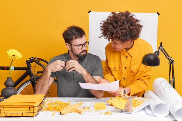 Concentrated woman and man collaborate on information pose at desktop during working time in modern office discuss architectural project surrounded by blueprints
