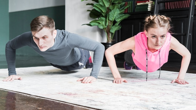 Concentrated woman and man doing push ups