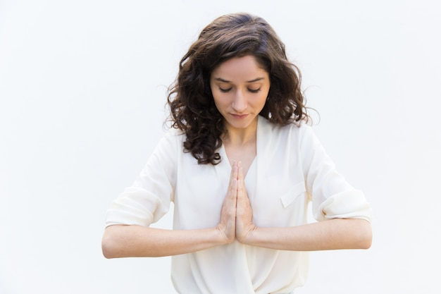 Concentrated woman meditating with hands in namaste gesture