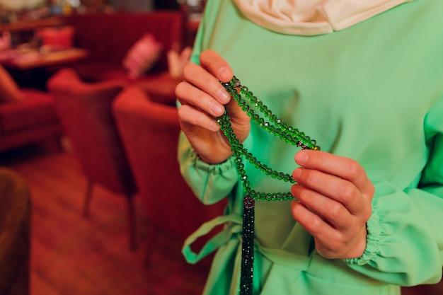 ロザリオビーズを身に着けて祈る集中女性。ナマステ。手を閉じます。