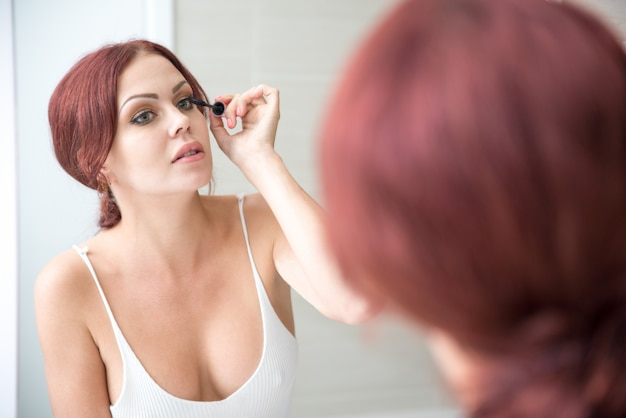 Concentrated woman putting on makeup at mirror