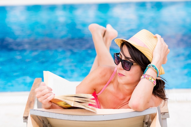 Concentrated woman reading on a deck chair