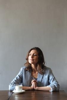 Сконцентрированная женщина сидя внутри помещения около чашки кофе