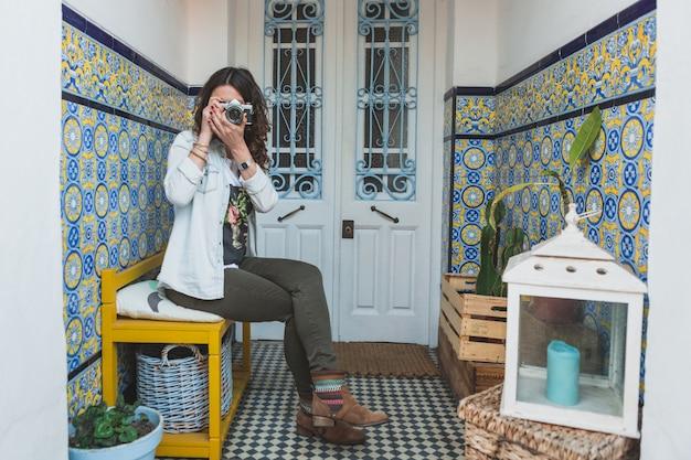 Donna concentrata di scattare una foto seduto su una panchina