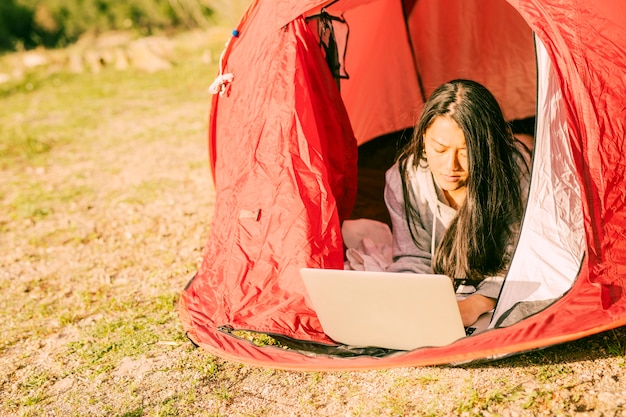 Concentrated woman using laptop lying in tent