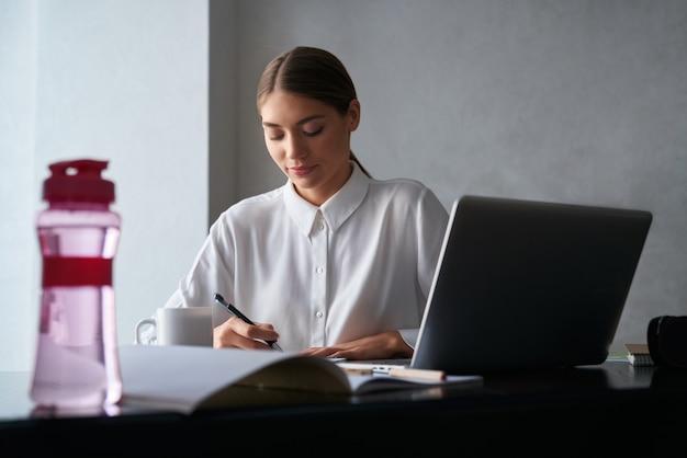 Donna concentrata che lavora al computer portatile durante il soggiorno a casa