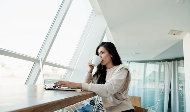 그녀의 노트북에서 작업 하 고 커피를 마시는 집중된 여자. 캐주얼 의류 개념입니다. 커피 하우스에서 일하고 음료를 즐기는 갈색 머리 여성 프리랜서. 자영업자.