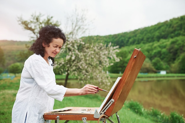 Concentrated at work. portrait of mature painter with black curly hair in the park outdoors