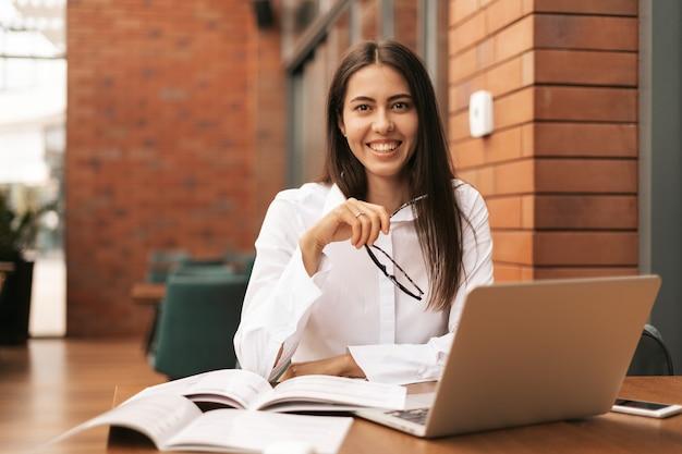 Concentrato sul lavoro. giovane bella donna che usa il suo computer portatile mentre è seduto. bella intelligente, carina, affascinante, attraente, elegante, proprietaria, ha una riunione online al chiuso