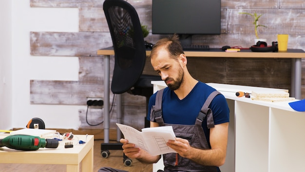 Concentrated worker reading assembly instruction for furniture. handyman helping owners with furniture assembly