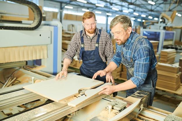 Сконцентрированные рабочие соединяя деревянные части на фабрике