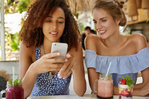 集中している若いアフリカ系アメリカ人女性は携帯電話でニュースをオンラインで読み、彼女の女性の友人は好奇心が強く、画面を見て、肯定的な表現をしています。レストランでリラックスした多民族の女性