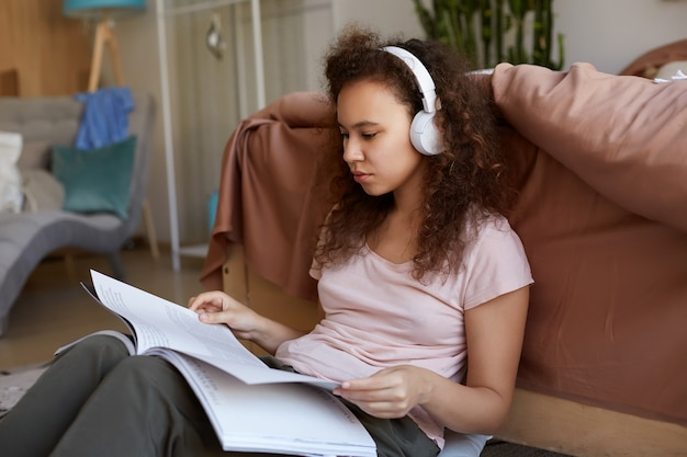 Concentrated young african american woman with curly hair siting in room, dressed in pajamas, listening his favorite music in headphones, reading new magazine.