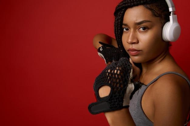 ヘッドフォンと赤いボクシンググローブに集中した若いアフリカのアスレチック女性ボクサー、直接ヒットするカメラを見て、コピースペースで色の背景の上に分離されました。武道の概念に連絡してください