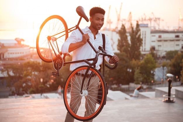 Concentrated young african man in early morning with bicycle
