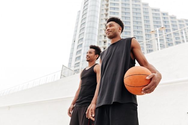 Giocatori di pallacanestro concentrati dei giovani uomini sportivi africani