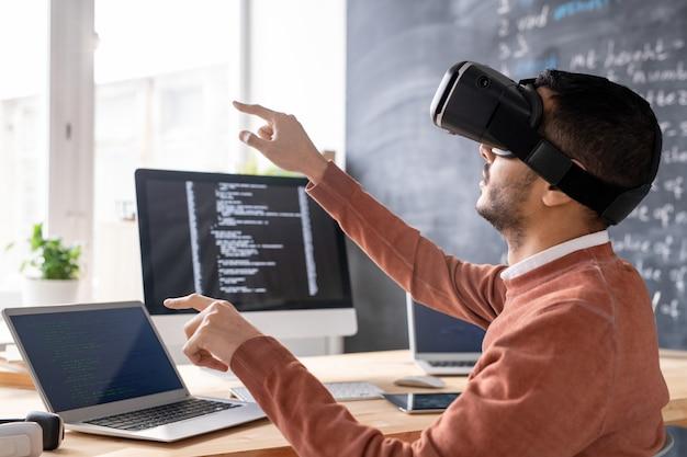 Сосредоточенный молодой арабский мужчина сидит в компьютерном офисе и разрабатывает приложение в очках виртуальной реальности