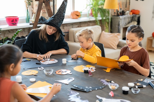 Concentrated young art teacher in witches hat sitting at table and drawing halloween pictures with kids while preparing paper decorations