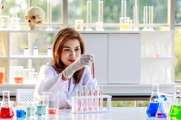 Concentrated young asian female chemistry student conducting experiment and examining samples of chemical substance in flasks during research process in laboratory.