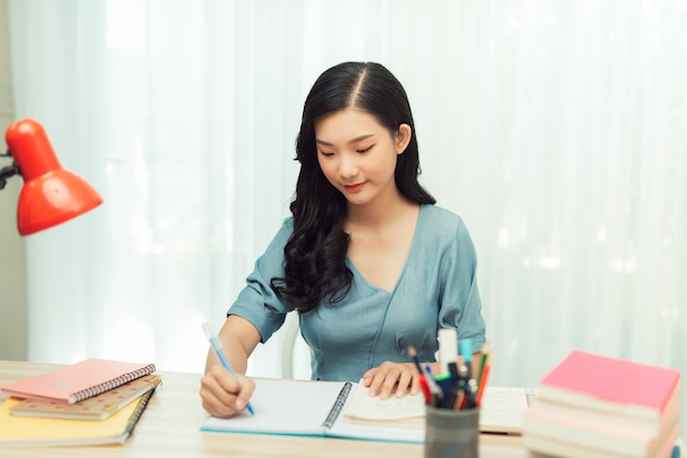 Concentrated young asian female student sitting at desk at home