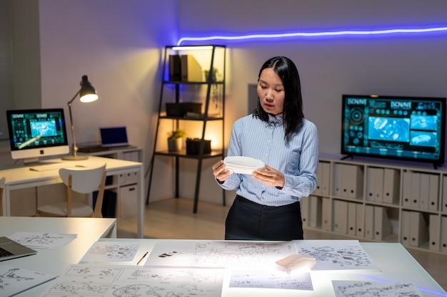 사무실에서 자동차 디자인을 생산하는 동안 레이아웃이 있는 책상에 서서 마케트를 들고 있는 정장 차림의 집중된 젊은 아시아 여성